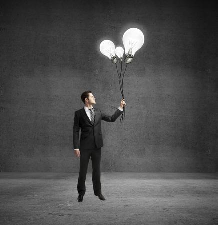 businessman holding flying light bulb photo