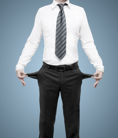empty pockets: businessman standing with pockets turned inside out on blue