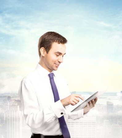 touch pad: businessman holding tablet on a city background