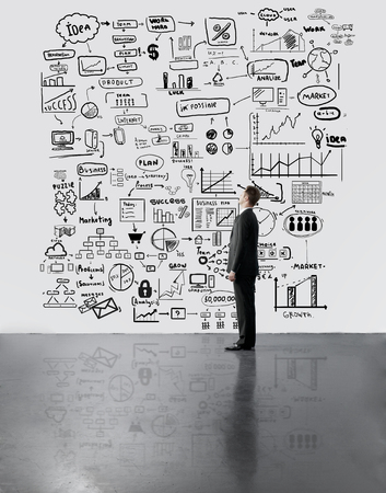 businessman looking at business concept on wall photo