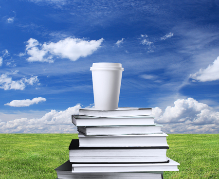book and cup of coffee on a background of nature photo