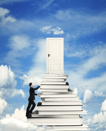 businessman climbing on stack of books with door photo
