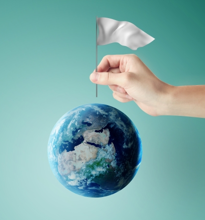 hand inserts a flag in earth photo