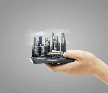 hand holding mobile phone with skyscraper on a gray  photo