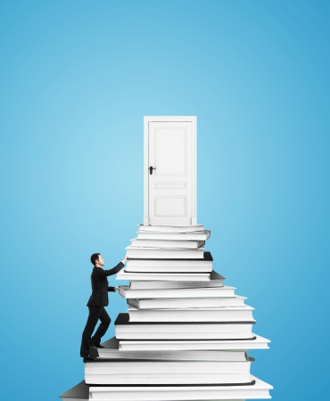 businessman  climbing on stack of books with door Stock Photo - 23510864