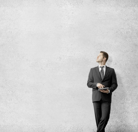 businessman with tablet looking at wall photo