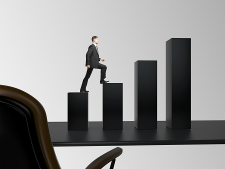 businessman climbing a chart column on table in office photo