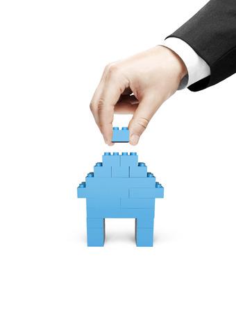 building blocks business: hand build house blocks on white background