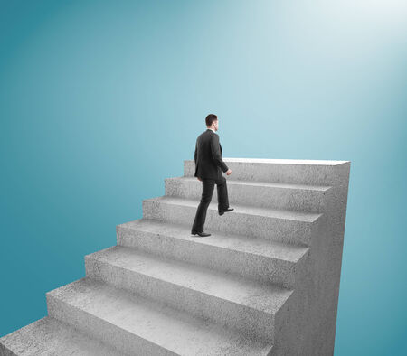 difficult journey: businessman climbing to stairs on blue background