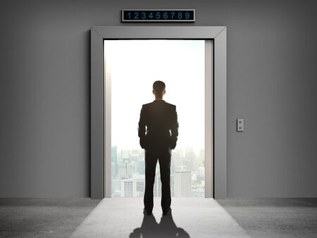 businessman looking at elevator to city photo