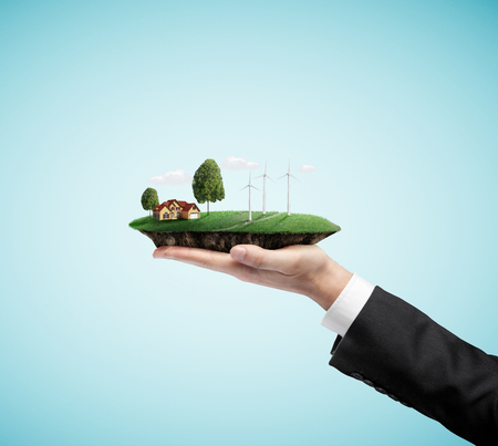 green building: businessman hand holding landscape with eco wind turbine Stock Photo