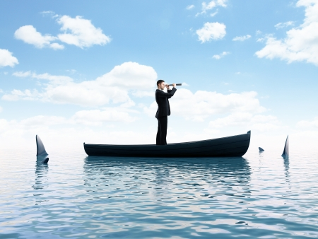 him: young man thinking  boat with sharks around him Stock Photo