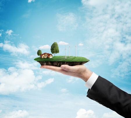 hand holding landscape with eco wind turbine Stock Photo - 23756101