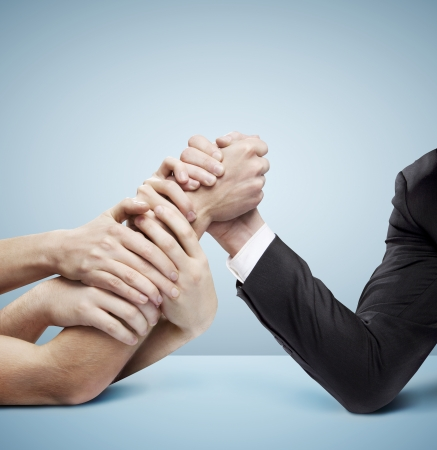 arm in arm: arm wrestling: businessman in opposition with many hands on blue background Stock Photo