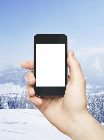 h�tte schnee: Hand h�lt Handy auf Winter Hintergrund Lizenzfreie Bilder