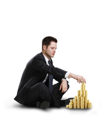 businessman sitting and building coin city on white background photo