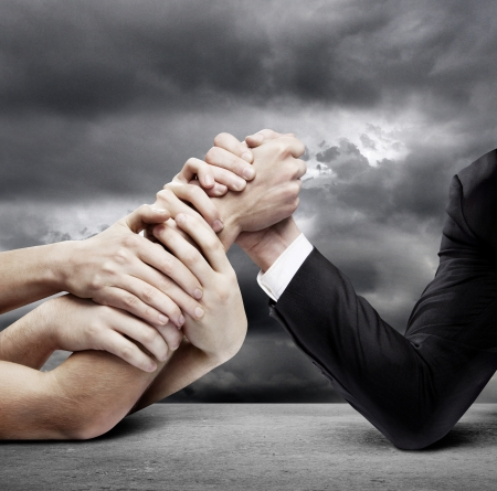 wrestling: arm wrestling: businessman in opposition with many hands Stock Photo