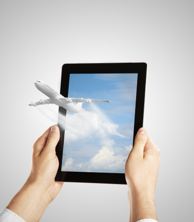 hand holding tablet with airplane photo