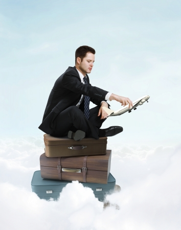 businessman sitting on suitcase with holding photo