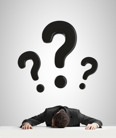 businessman sleeping on table and question mark over head photo