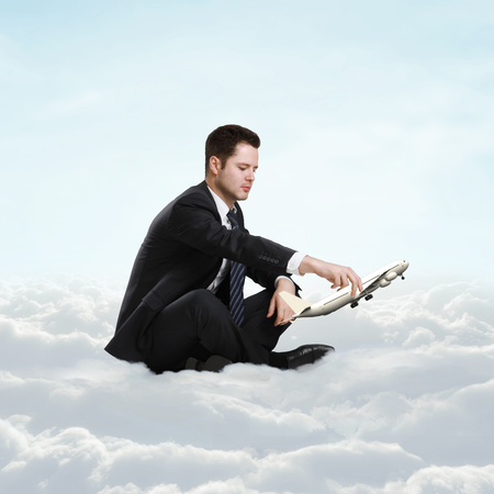 businessman sitting on cloud and holding photo