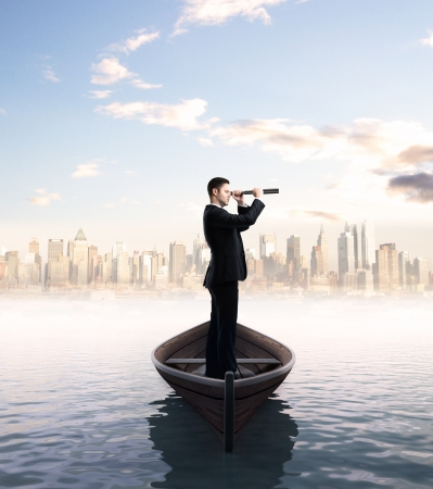 business trip: businessman looking through a telescope and city