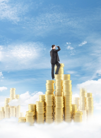 businessman climbing on gold coin tower photo