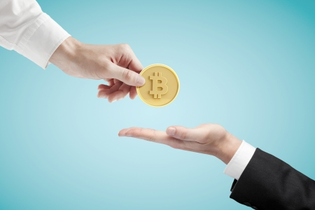 hand giving bitcoin on a blue background