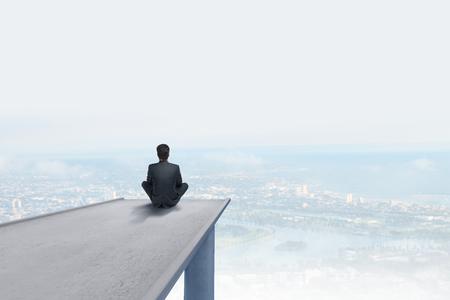 quiet scenery: businessman sitting on concrete bridge an looking clouds