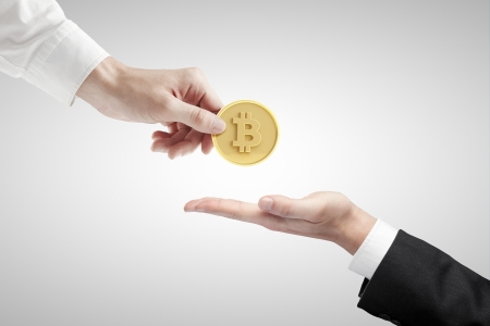hand giving bitcoin on a gray background