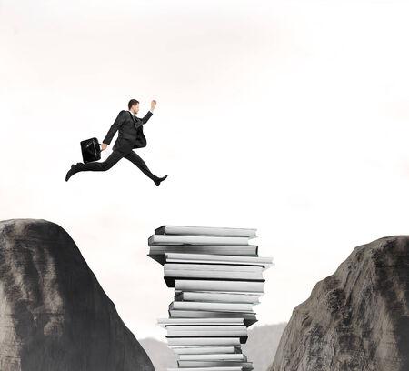 businessman jumping: Businessman jumping from a rock through books