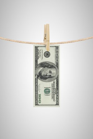 dollar bill is hanging on a rope with wooden clothespin photo