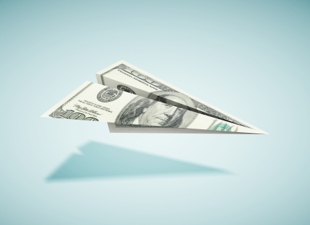 paper dollar plane on a blue background photo