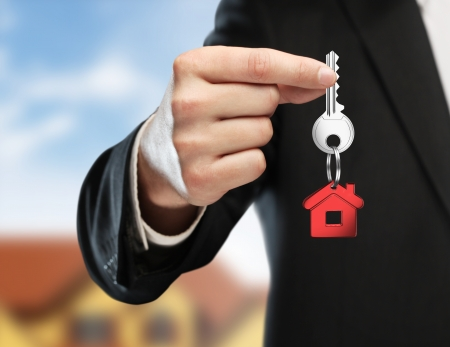 hand handing key on cottage background photo