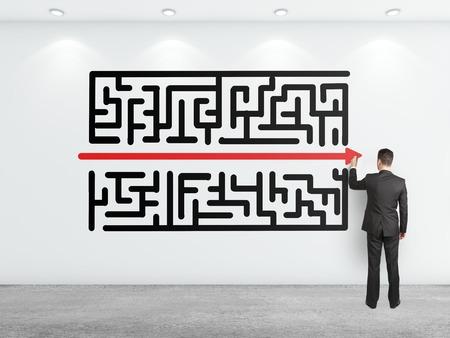 maze: businessman drawing maze on white wall