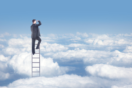 businessman standing on ladder and looking too sky photo