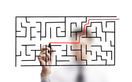 labyrinth: businessman drawing labyrinth on a white background