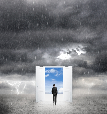 bad weather: businessman walking to opened door from bad weather to white Stock Photo