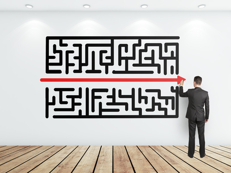 young businessman drawing maze on white wall photo