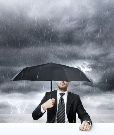 Businessman with umbrella in rain Stock Photo - 24801157