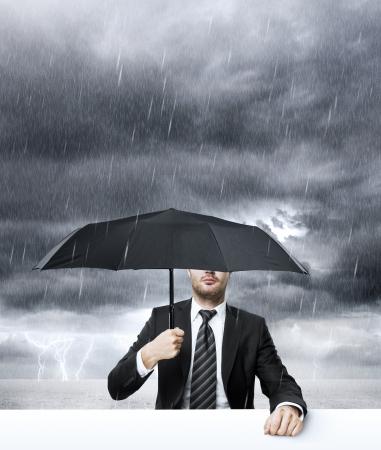 Businessman with umbrella in rain Stock Photo - 24801157
