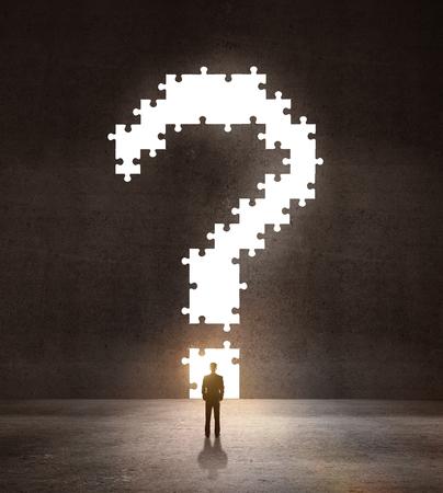 businessman looking an big question mark on wall