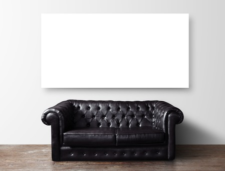 black leather sofa in room and blank poster on wall photo