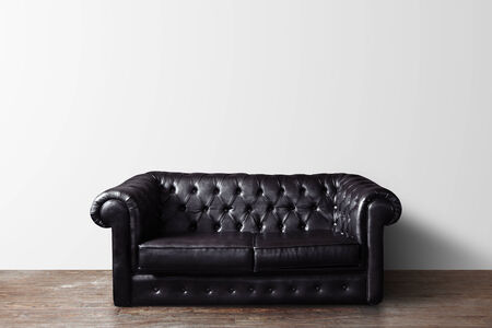 cracked concrete frame: black leather sofa in room