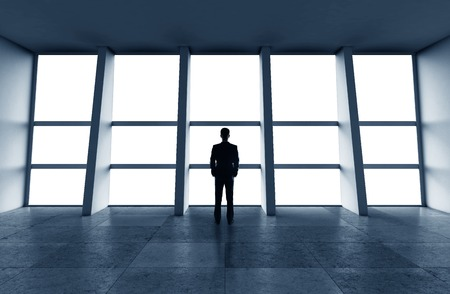 businessman standing in office and looking in city photo