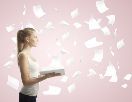 woman holding book with flying around paper photo