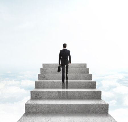 altitude: businessman climbing to stairs on sky background Stock Photo