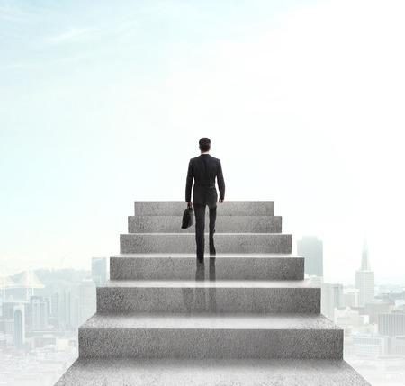 都市の背景に階段を登る実業家