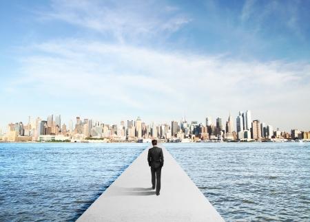 businessman in suit walking to city on concrete bridg