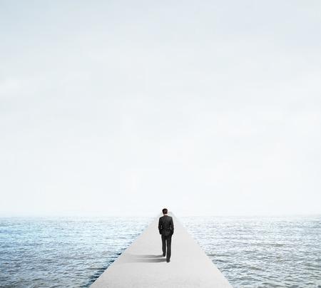 incentive: businessman in suit walking on concrete bridg Stock Photo